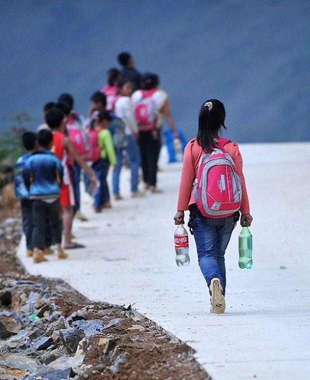 4月21日,在广西凌云县伶站瑶族乡浩坤村,孩子带水去学校。新华社记者 黄孝邦 摄   广西凌云县伶站瑶族乡浩坤村弄新小学位于大石山区深处,自然环境恶劣,由于学校附近没有水源,很多时候学校生活用水需要购买或是靠县里有关部门送水,学校一年至少花费四五千元用来买水。每个学生每天从学校取一瓶水用于淘米洗碗、刷牙洗脸,学生们在校寄宿时无法洗澡洗衣服。另外,很多学生每周一从家里自带一两瓶水作为一个星期寄宿生活的饮用水。