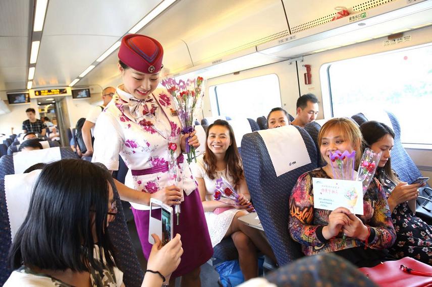 5月12日,在成都开往营山的D5154次动车组列车上,动车乘务员正在为身为人母的旅客赠送康乃馨。