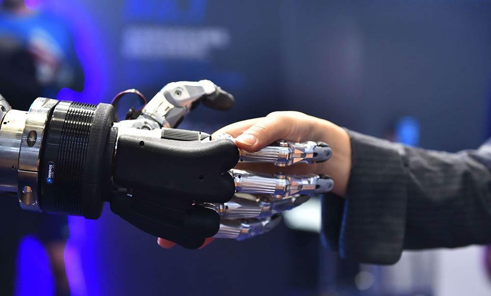 参观者试着和仿人五指机械手握手