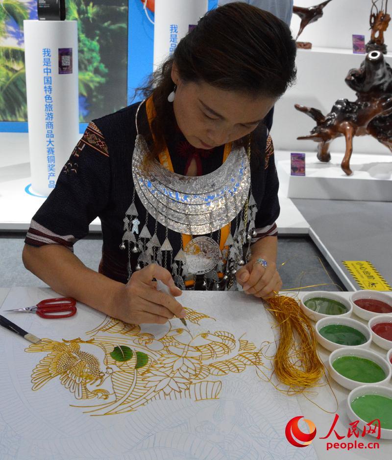 消博会海南馆内,工艺美术师正在绘制景泰蓝掐丝珐琅画。人民网记者 杜燕飞摄
