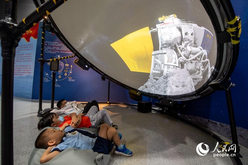 """全国科普日勾当11日在全国各地启动。中国科技馆主会场内,几位小伴侣在探月体验区陶醉式体验""""月球挖土""""进程。太平洋在线记者 翁奇羽摄"""